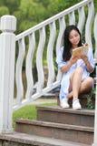 Libro de lectura chino de la muchacha La mujer joven hermosa rubia con el libro se sienta en los pasos del pabellón Foto de archivo libre de regalías