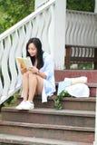 Libro de lectura chino de la muchacha La mujer joven hermosa rubia con el libro se sienta en los pasos del pabellón Fotos de archivo libres de regalías