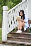 Libro de lectura chino de la muchacha La mujer joven hermosa rubia con el libro se sienta en los pasos del pabellón Imagen de archivo libre de regalías