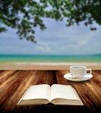 Libro de lectura con la taza caliente en la isla Foto de archivo libre de regalías