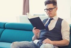 Libro de lectura contento del hombre en el sofá imagenes de archivo