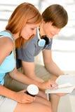 Libro de lectura de dos estudiantes universitarios mientras que se sienta Foto de archivo