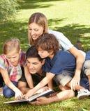 Libro de lectura de dos niños con la familia Imagenes de archivo