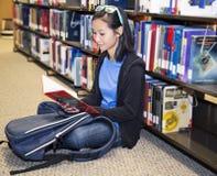 Libro de lectura de la biblioteca de la chica joven Fotos de archivo libres de regalías