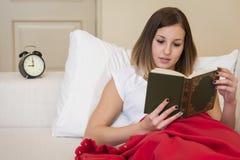 Libro de lectura de la cama de la mujer Foto de archivo