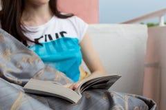 Libro de lectura de la chica joven con sonrisa, primer Imágenes de archivo libres de regalías