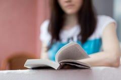Libro de lectura de la chica joven con sonrisa, primer Imagen de archivo libre de regalías