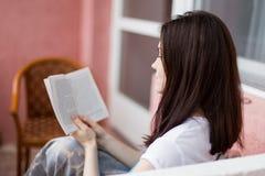 Libro de lectura de la chica joven con sonrisa, primer Fotos de archivo libres de regalías