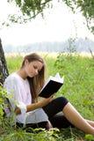 Libro de lectura de la chica joven en parque Foto de archivo libre de regalías