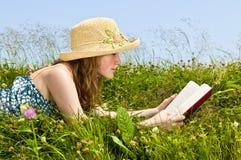Libro de lectura de la chica joven en prado Foto de archivo