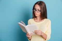 Libro de lectura de la chica joven sobre fondo azul Fotos de archivo libres de regalías