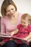 Libro de lectura de la hija de la madre y del bebé Fotografía de archivo
