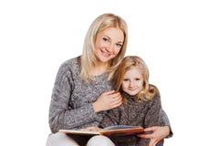 Libro de lectura de la madre con la hija joven Imagen de archivo libre de regalías