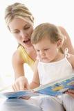 Libro de lectura de la madre y del bebé dentro Foto de archivo libre de regalías