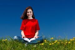 Libro de lectura de la muchacha al aire libre Imágenes de archivo libres de regalías