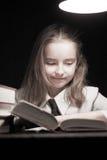 Libro de lectura de la muchacha bajo la lámpara Imagenes de archivo