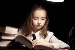 Libro de lectura de la muchacha bajo la lámpara Fotos de archivo libres de regalías