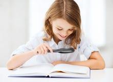 Libro de lectura de la muchacha con la lupa en la escuela Imagen de archivo