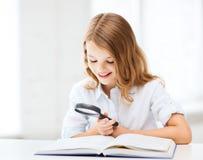 Libro de lectura de la muchacha con la lupa en la escuela Fotografía de archivo