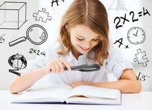 Libro de lectura de la muchacha con la lupa en la escuela Fotografía de archivo libre de regalías