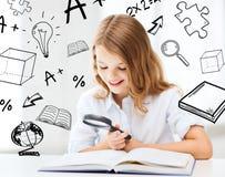 Libro de lectura de la muchacha con la lupa en la escuela Fotos de archivo libres de regalías
