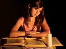 Libro de lectura de la muchacha con la vela. Imágenes de archivo libres de regalías