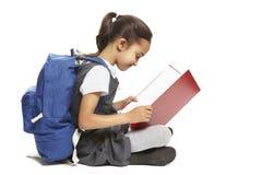 Libro de lectura de la muchacha de la escuela que se sienta Imagen de archivo libre de regalías