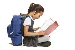 Libro de lectura de la muchacha de la escuela que se sienta Fotografía de archivo