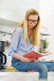 Libro de lectura de la muchacha del adolescente en cocina Foto de archivo libre de regalías
