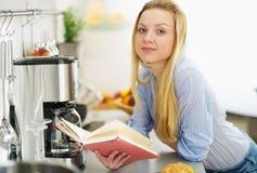 Libro de lectura de la muchacha del adolescente en cocina Fotografía de archivo libre de regalías