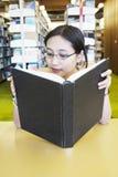Libro de lectura de la muchacha del empollón en la biblioteca Imágenes de archivo libres de regalías
