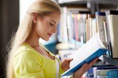 Libro de lectura de la muchacha del estudiante de la High School secundaria en la biblioteca Foto de archivo