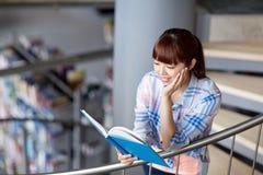 Libro de lectura de la muchacha del estudiante de la High School secundaria en la biblioteca Foto de archivo libre de regalías