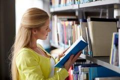 Libro de lectura de la muchacha del estudiante de la High School secundaria en la biblioteca Imagen de archivo libre de regalías