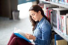 Libro de lectura de la muchacha del estudiante de la High School secundaria en la biblioteca Imagenes de archivo