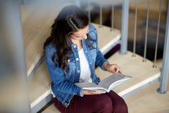 Libro de lectura de la muchacha del estudiante de la High School secundaria en las escaleras Imagen de archivo libre de regalías