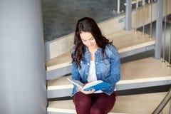 Libro de lectura de la muchacha del estudiante de la High School secundaria en las escaleras Imagenes de archivo