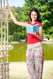 Libro de lectura de la muchacha del estudiante en el lago delantero Foto de archivo libre de regalías