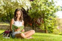 Libro de lectura de la muchacha del estudiante que se sienta en hierba Imágenes de archivo libres de regalías