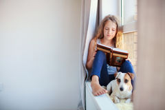 Libro de lectura de la muchacha en casa Imagen de archivo libre de regalías