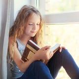 Libro de lectura de la muchacha en casa Fotografía de archivo