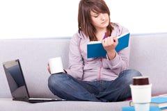Libro de lectura de la muchacha en el sofá Imagenes de archivo