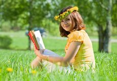 Libro de lectura de la muchacha en hierba Fotos de archivo