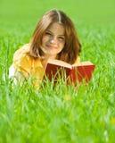 Libro de lectura de la muchacha en hierba Imágenes de archivo libres de regalías