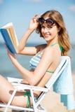 Libro de lectura de la muchacha en la silla de playa Fotografía de archivo