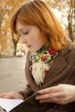 Libro de lectura de la muchacha en parque del otoño Foto de archivo libre de regalías