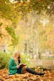 Libro de lectura de la muchacha en parque del otoño Foto de archivo