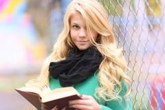 Libro de lectura de la muchacha en parque del otoño Imágenes de archivo libres de regalías