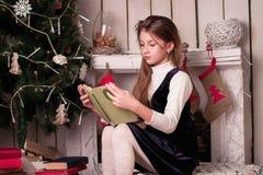 Libro de lectura de la muchacha entre las decoraciones del Año Nuevo Foto de archivo libre de regalías