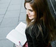 Libro de lectura de la muchacha/estudiante que lee un libro en parque/ Imagen de archivo libre de regalías